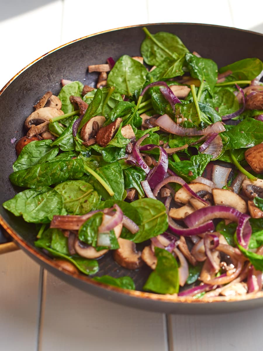 Onions mushrooms spinach in pan