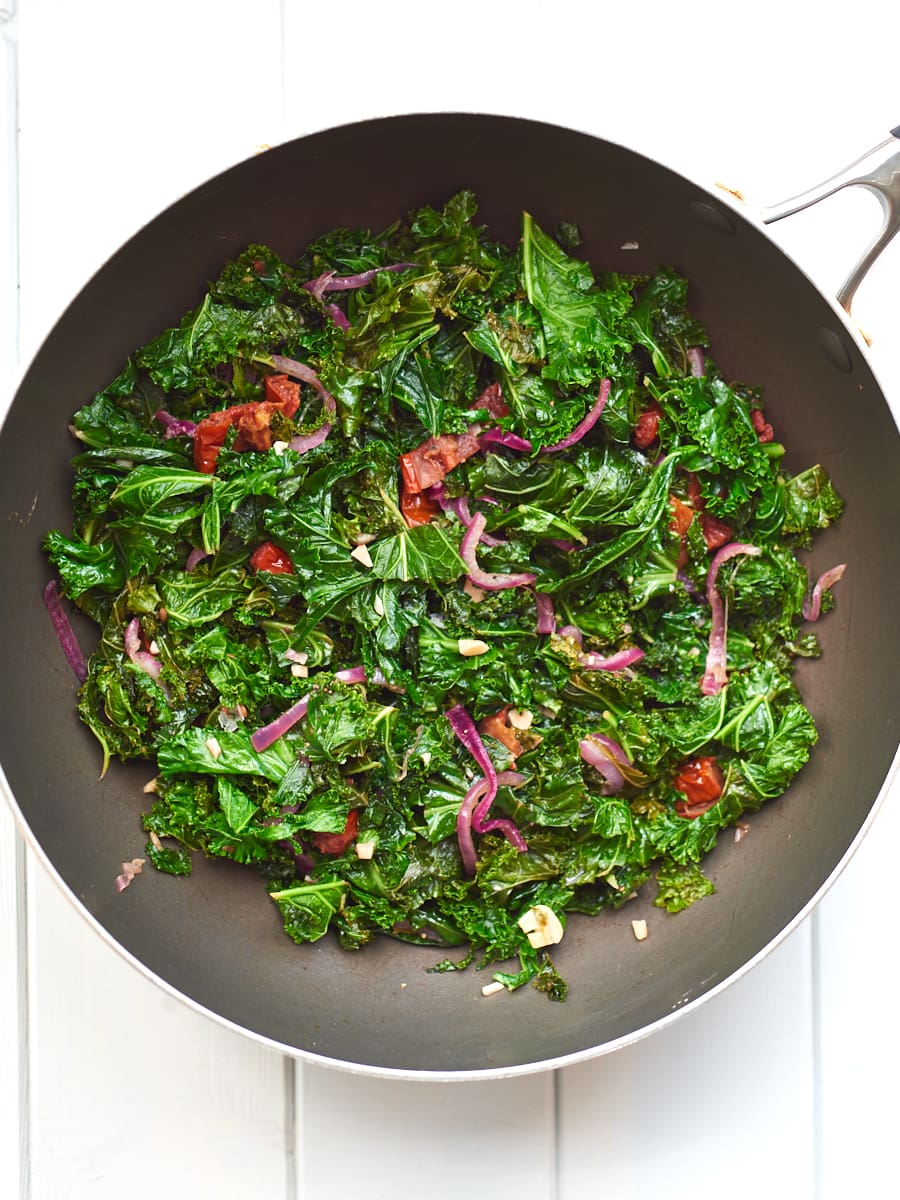 Sauteed kale with garlic and sundried tomatoes in pan