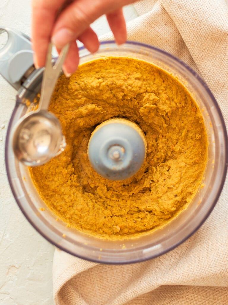 Adding water to homemade hummus