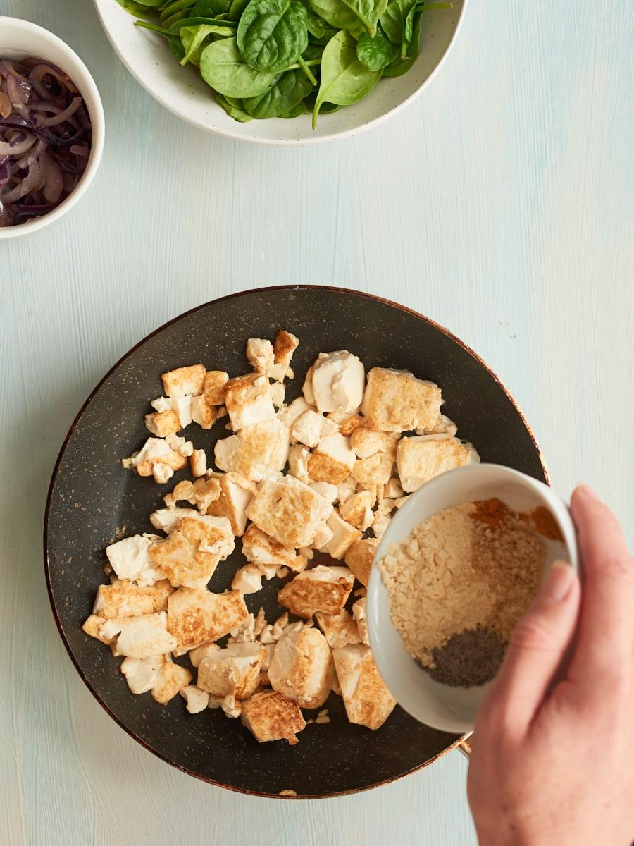 adding spices to vegan scramble