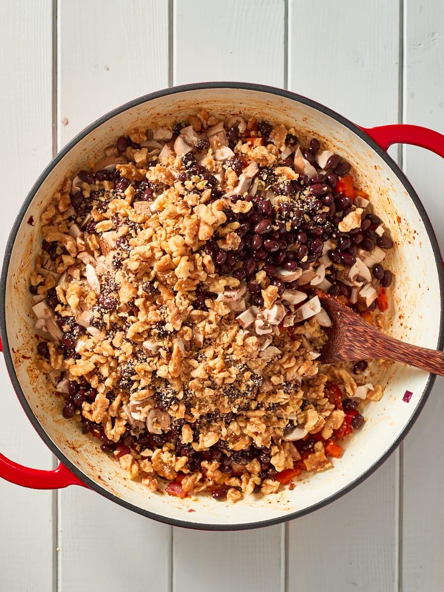 Adding walnuts to pot with chilli non carne