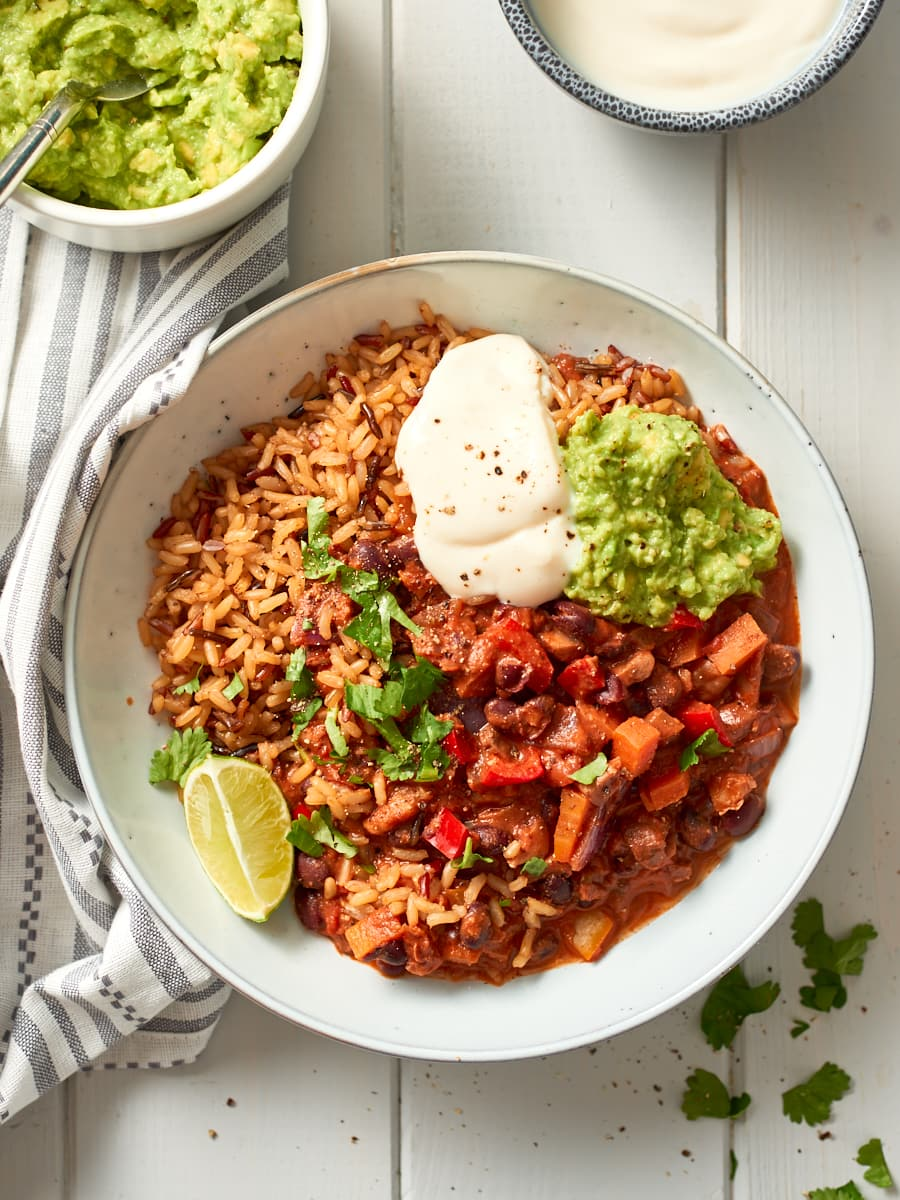 overhead photo of bowl of chilli non carne with guac and soured cream