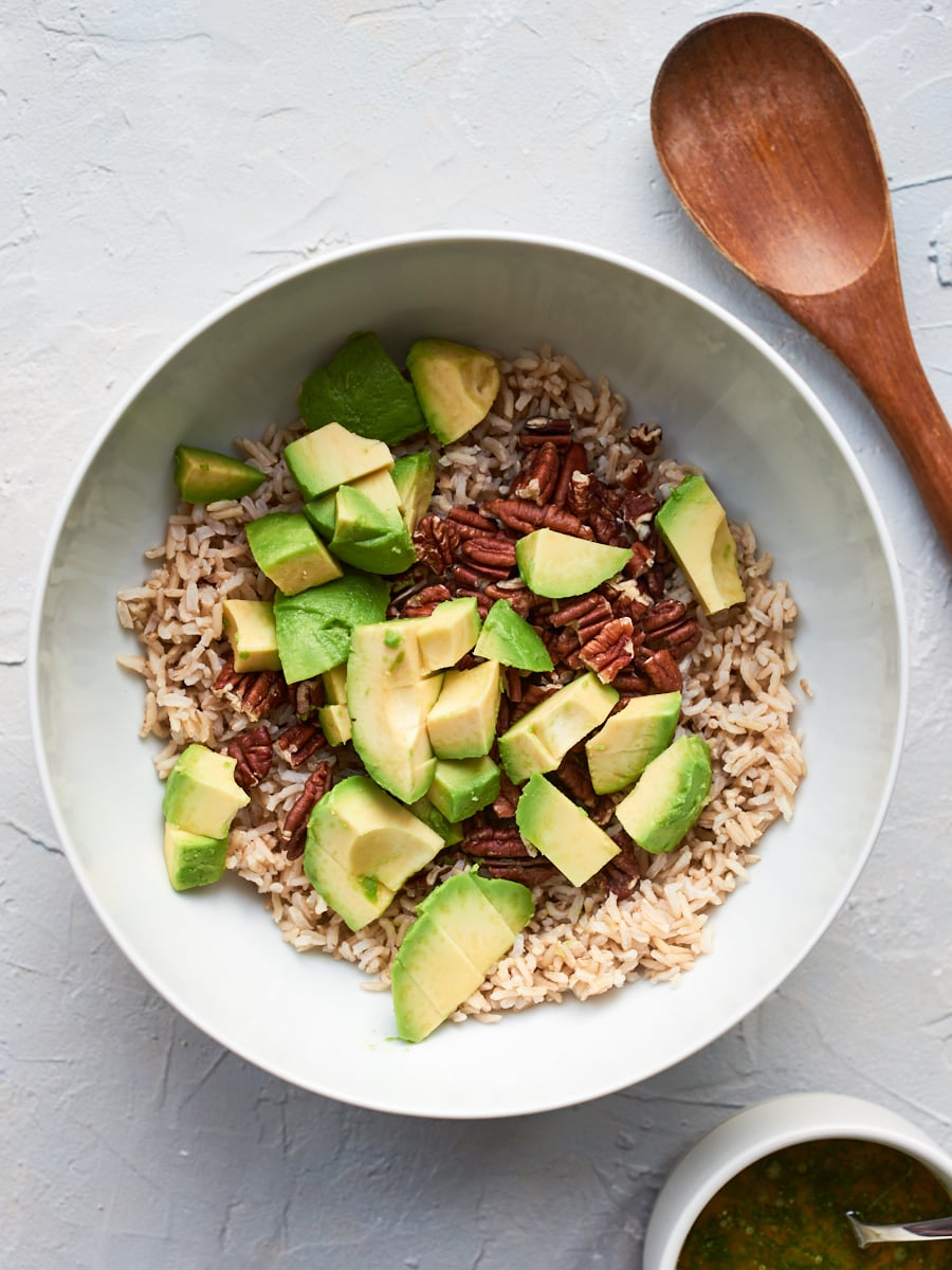 adding avocado to brown rice and pecans