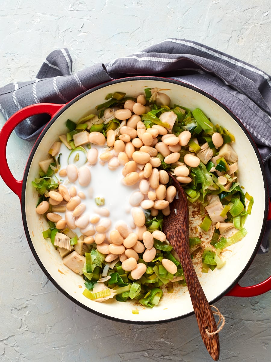 adding coconut milk and butterbeans to pan