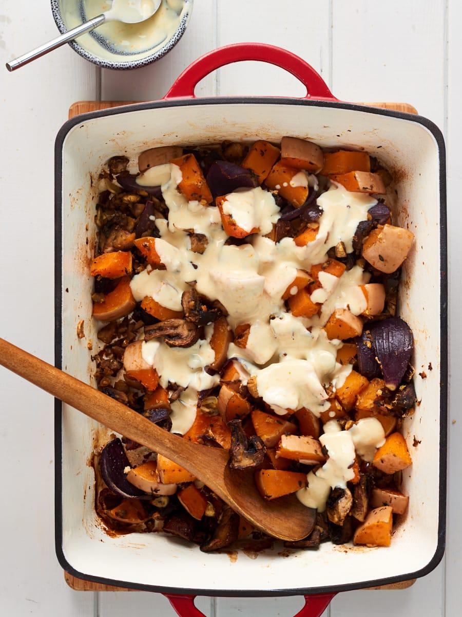 Adding yoghurt orange dressing to butternut squash traybake