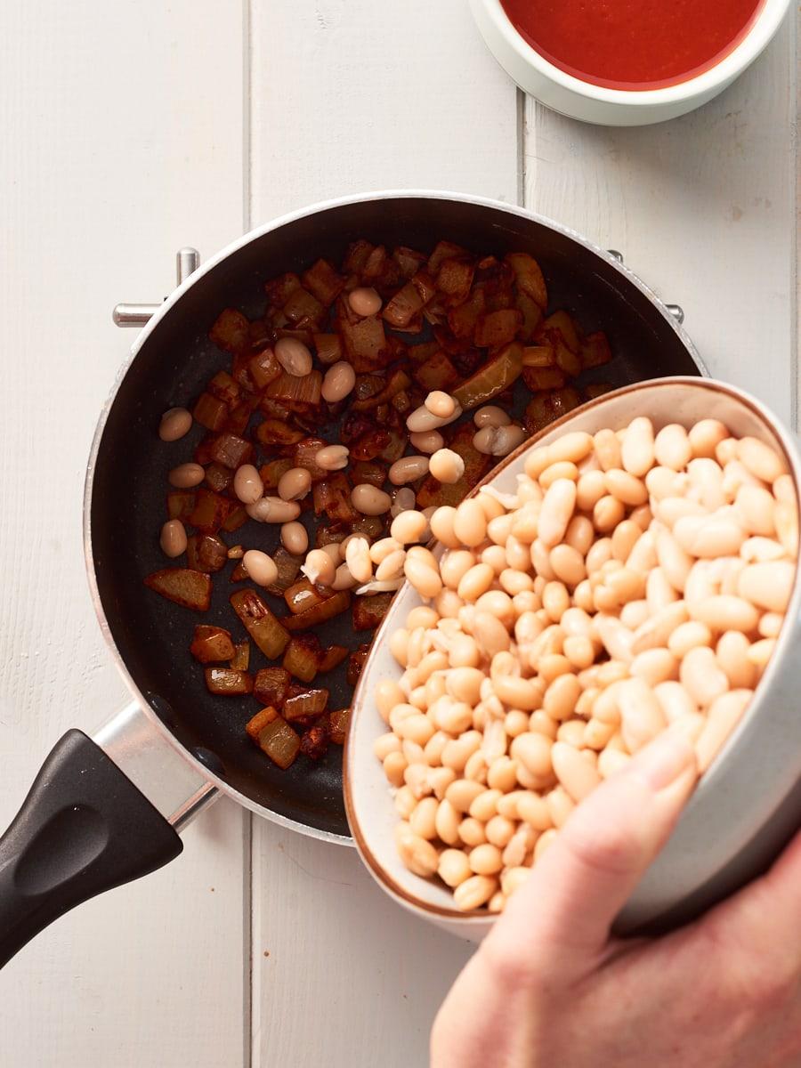 adding white beans to pan