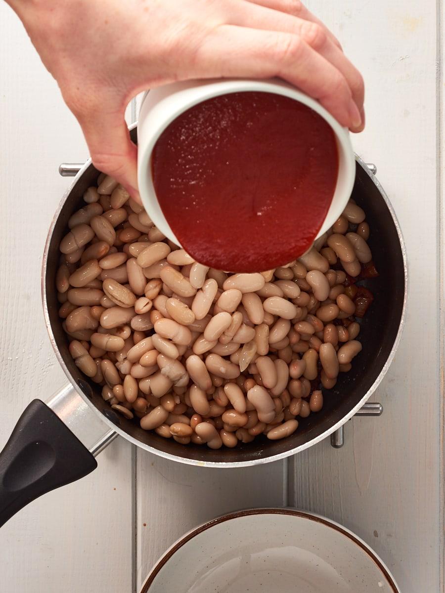 adding tomato passata to pan