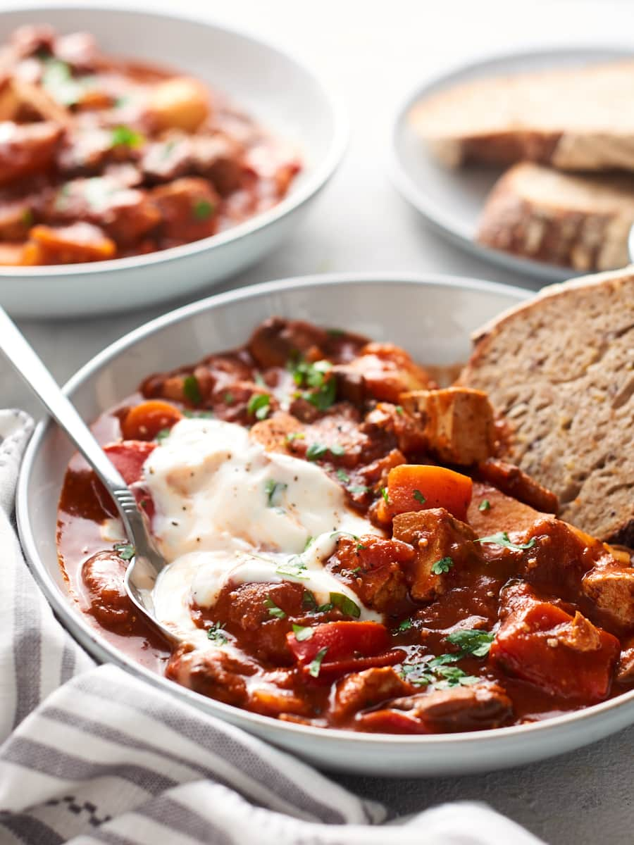 Bowl of vegan goulash with bread dipped in