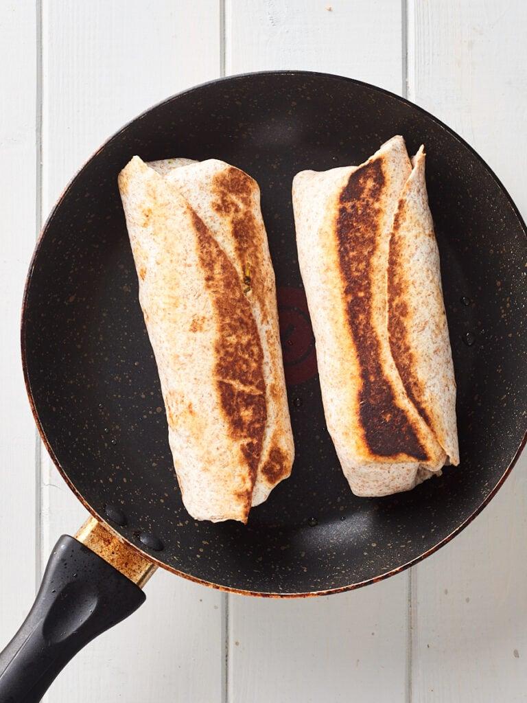 Sealing tofu breakfast burritos in pan