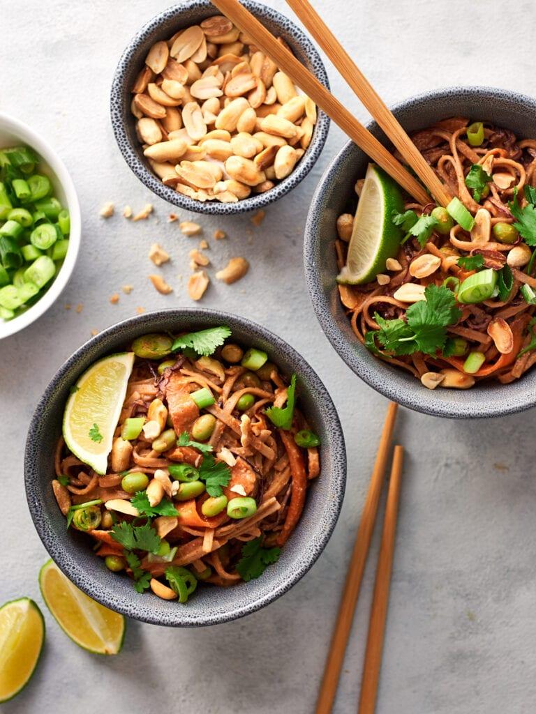 Two bowls of vegan peanut noodles with chopsticks