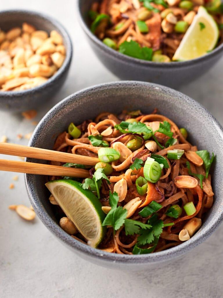 Two bowls of vegan peanut noodles with chopsticks 2