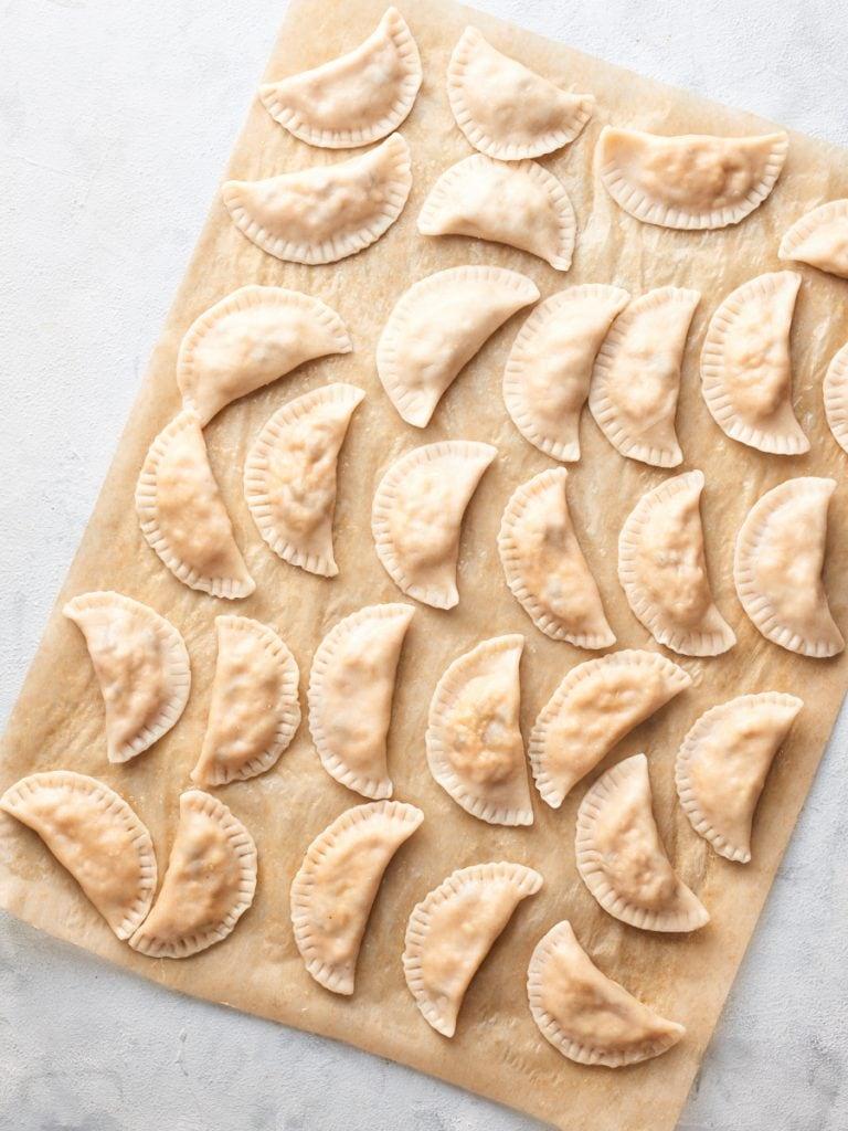Boiled pierogi on a baking sheet