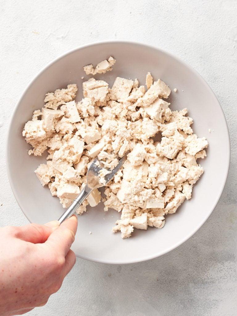 Mashing up tofu for vegan cottage cheese filling