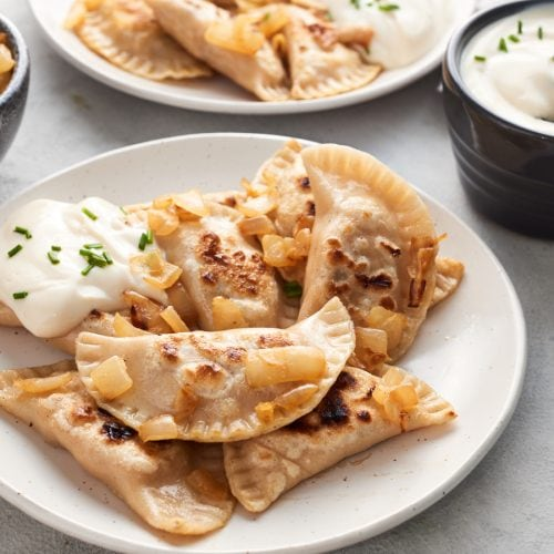 Two plates of vegan pierogi with vegan sour cream