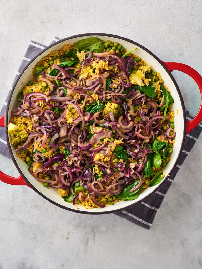 Topping the green biryani with cooked onions