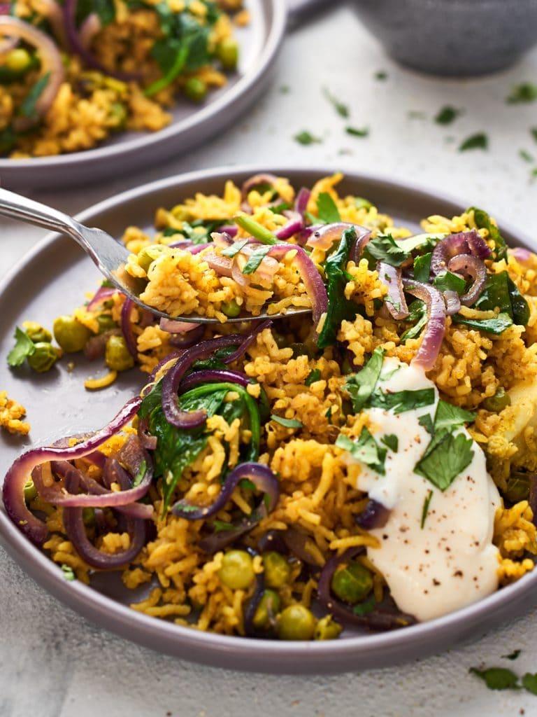 A forkful of vegan biryani and two plates