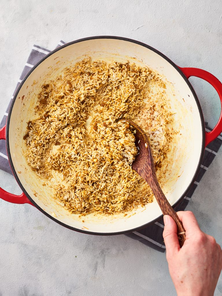Adding dried rice to the garlic and spices and toasting