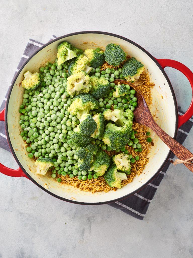 Adding peas and broccoli to the pan