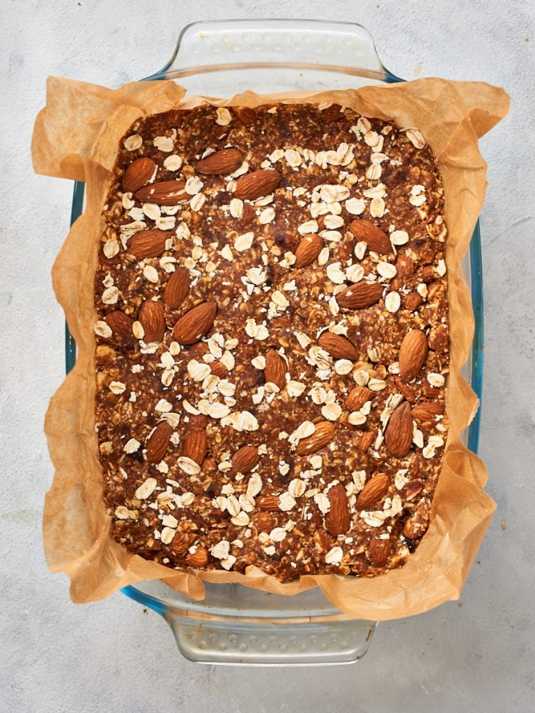 Pressing almonds and oats into the top of bars before baking