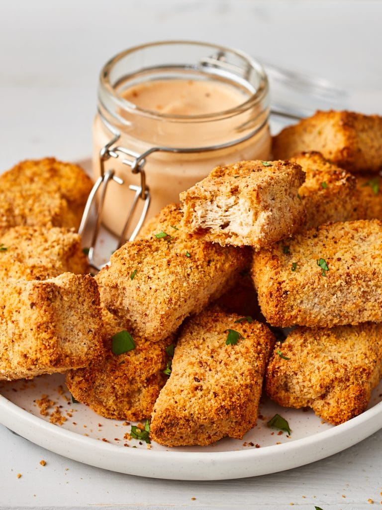 Pile of tofu chicken nuggets and jar of dip, with one tofu nugget torn open to show texture