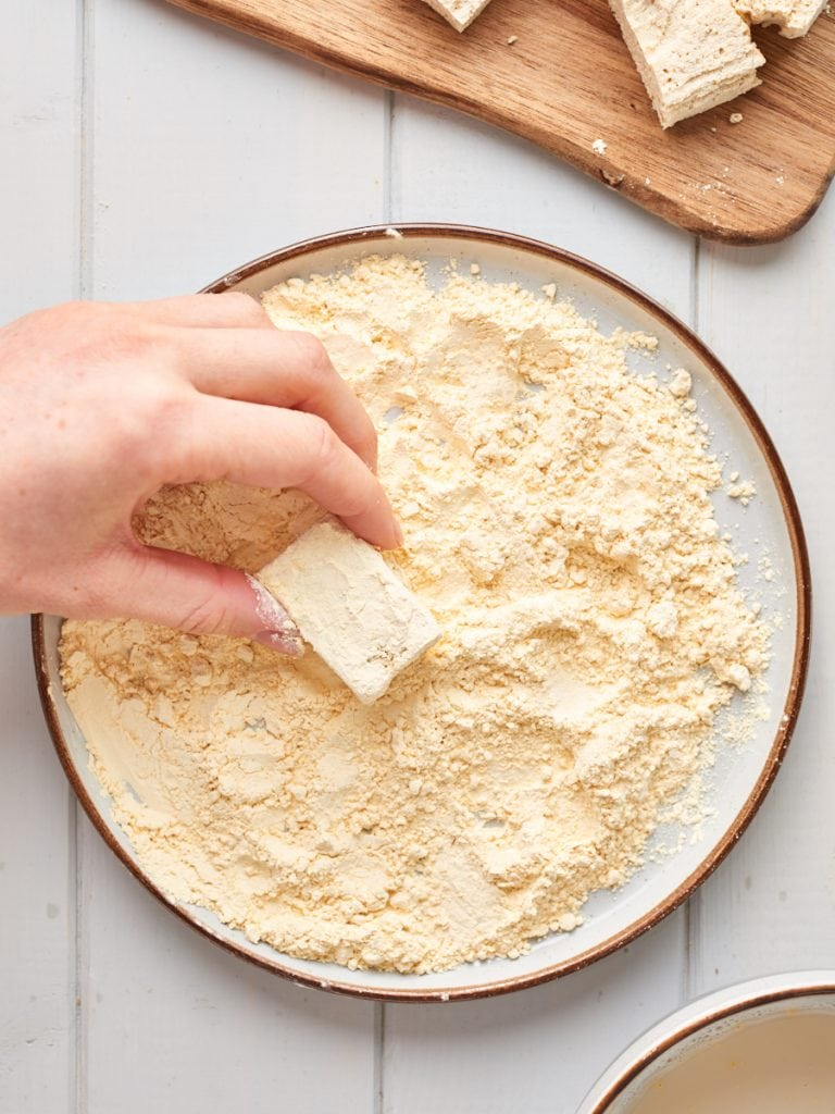 Rolling chunk of tofu in chickpea flour