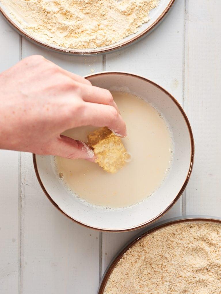 Dipping chunk of tofu in milk