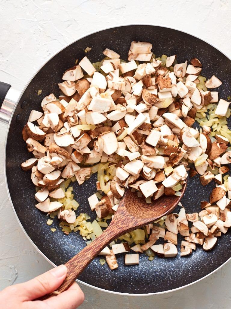 adding mushrooms to the pan