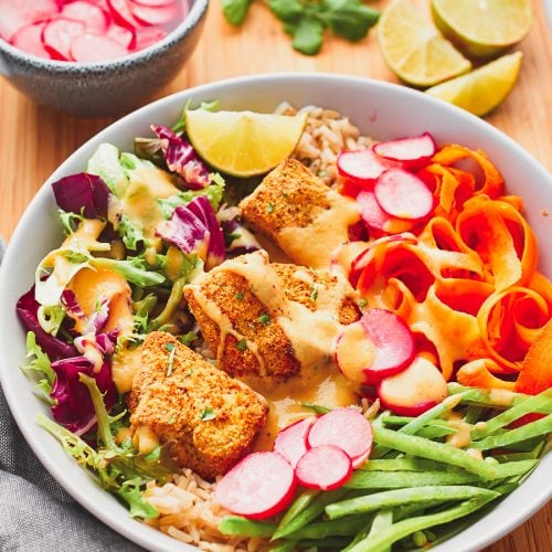 Bowl of tofu katsu salad with lime, coriander, and pickled radish on the side
