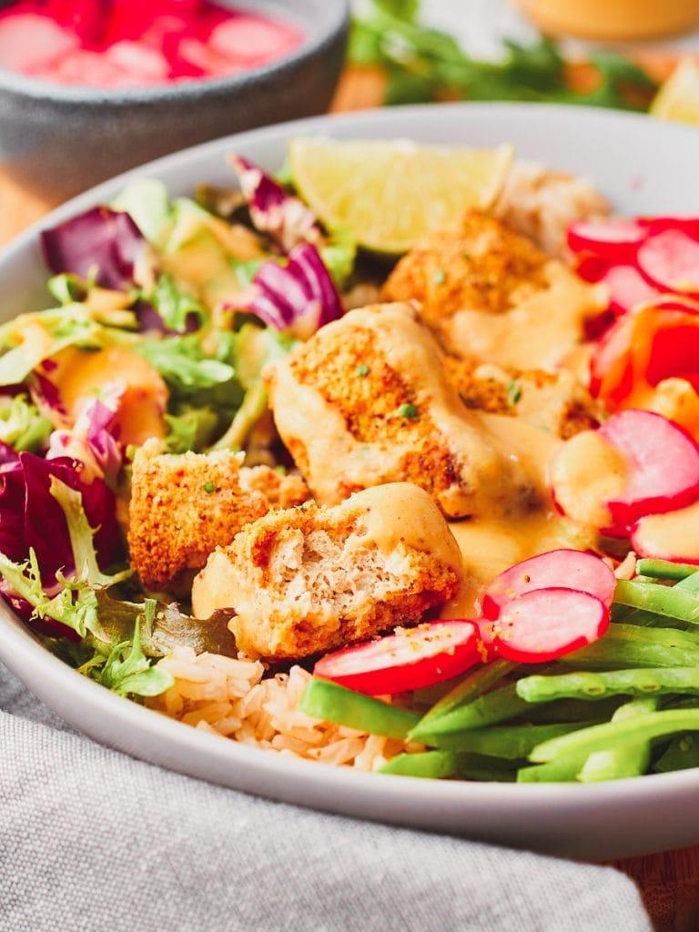 Tofu katsu salad with one piece fo tofu katsu cut open