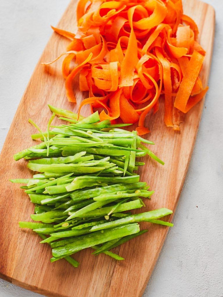 Ribboned carrots and mangetout on a chopping board