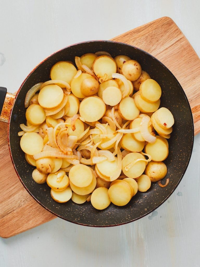 Potatoes and onion in a flat layer in the vegan tortilla pan