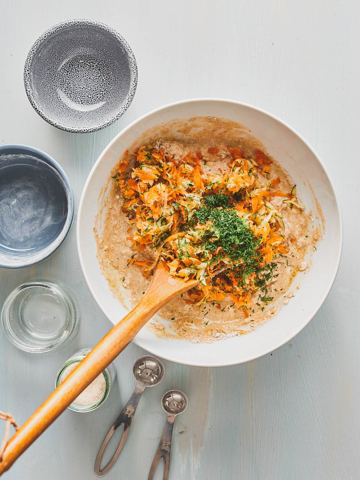 Adding the grated vegetables and dill to the mixing bowl