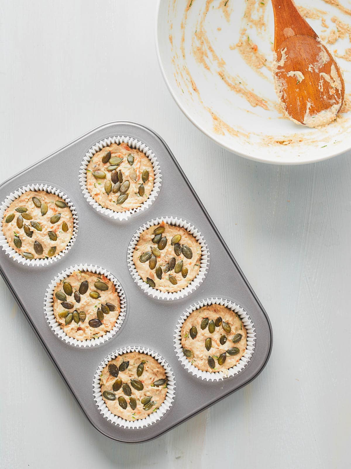 Topping the muffins with pumpkin seeds