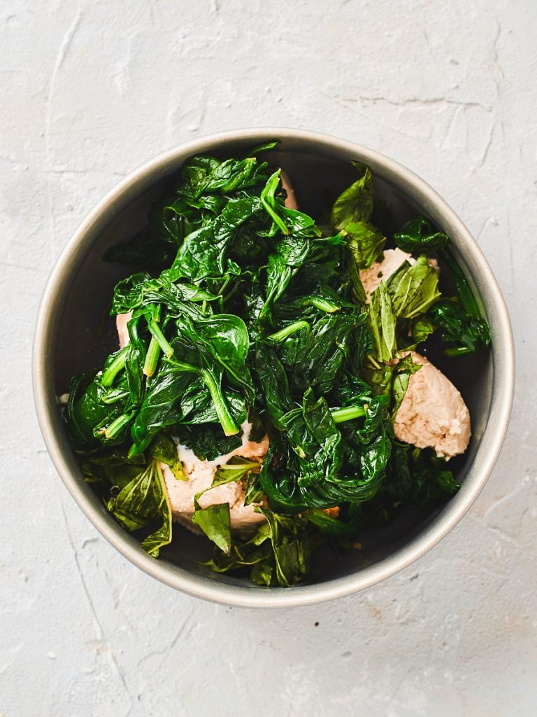 Adding the wilted spinach to the bowl