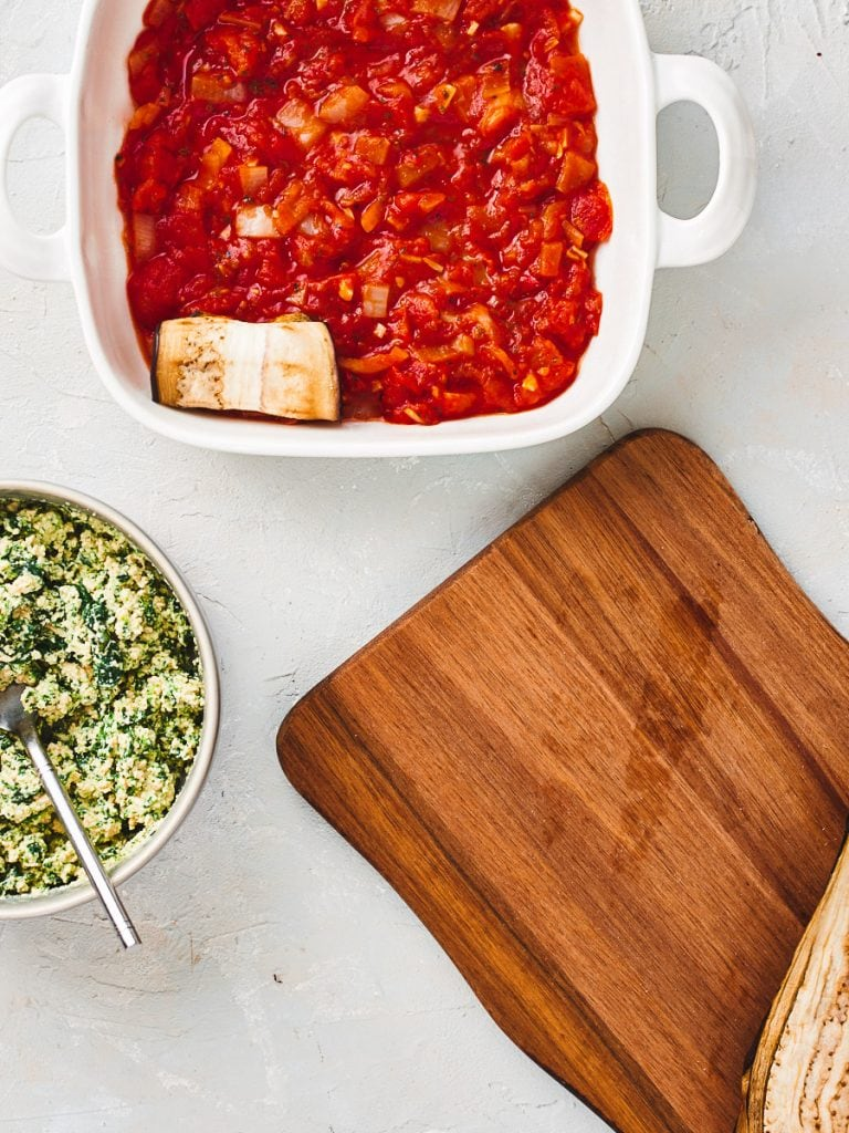 One eggplant cannelloni in baking dish with tomato sauce