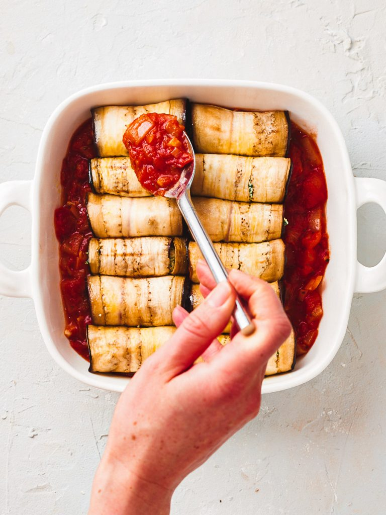 Spooning the tomato sauce over the eggplant roll ups