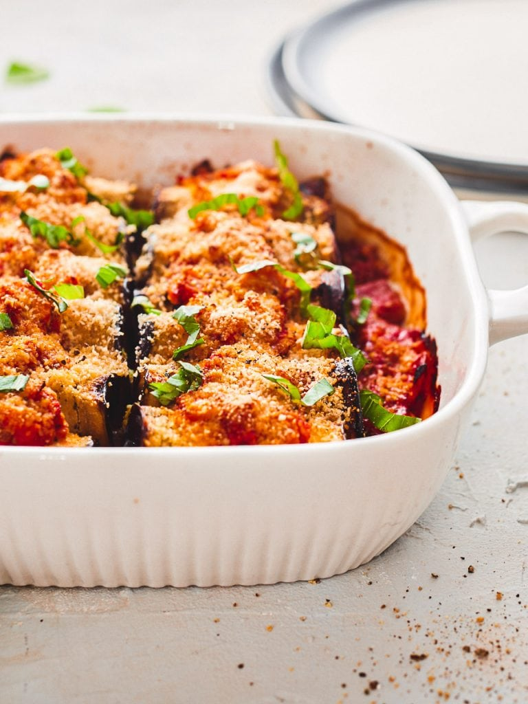 Baked eggplant cannelloni in a dish, topped with basil
