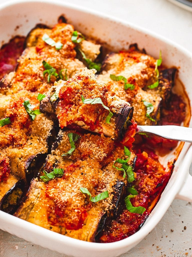 Vegan eggplant cannelloni being lifted out of baking dish