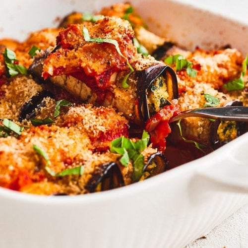 An eggplant cannelloni being lifted out of the oven dish