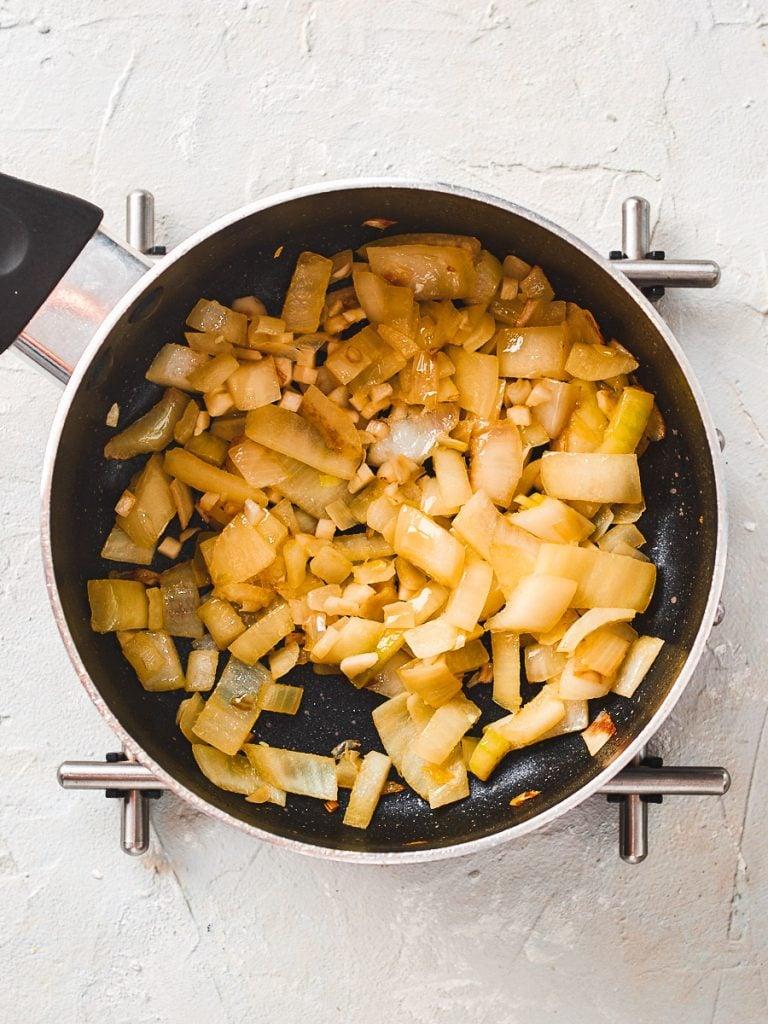 Chopped onion and garlic frying in saucepan