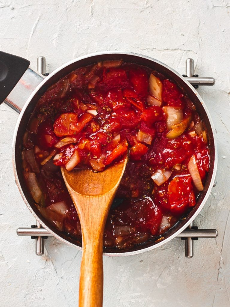 Stirring homemade tomato sauce in pan