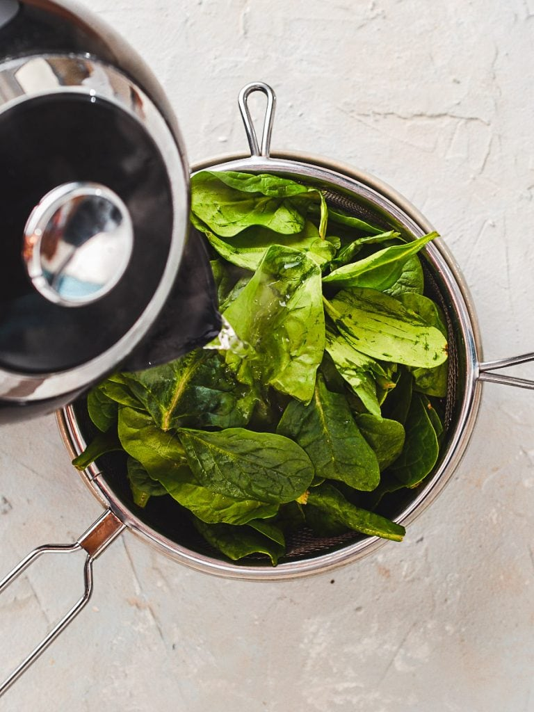 Pouring boiling water over the spinach to wilt it