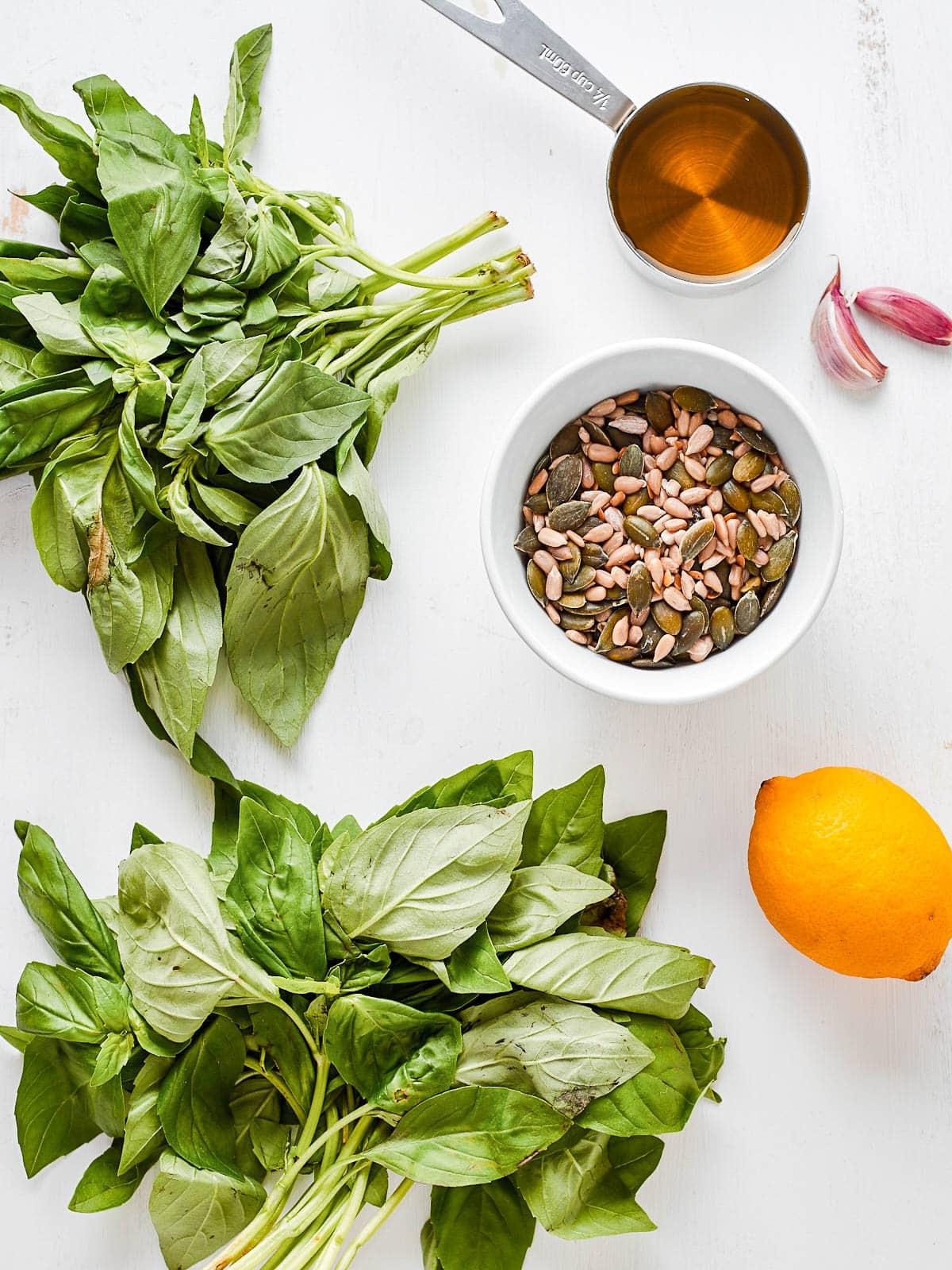 Ingredients for homemade pesto- basil, olive oil, garlic, seeds, lemon