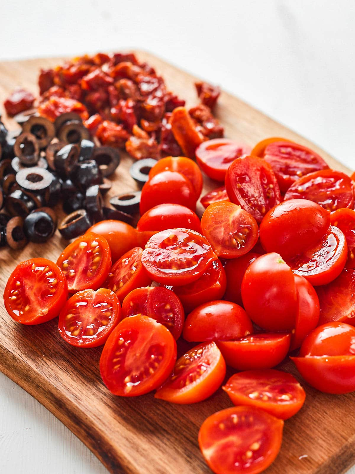 Chopped tomatoes, olives and sun dried tomatoes on a chopping board