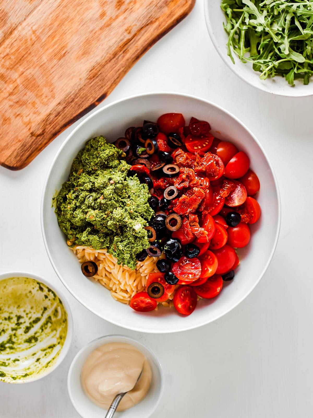 Adding pesto to mixing bowl