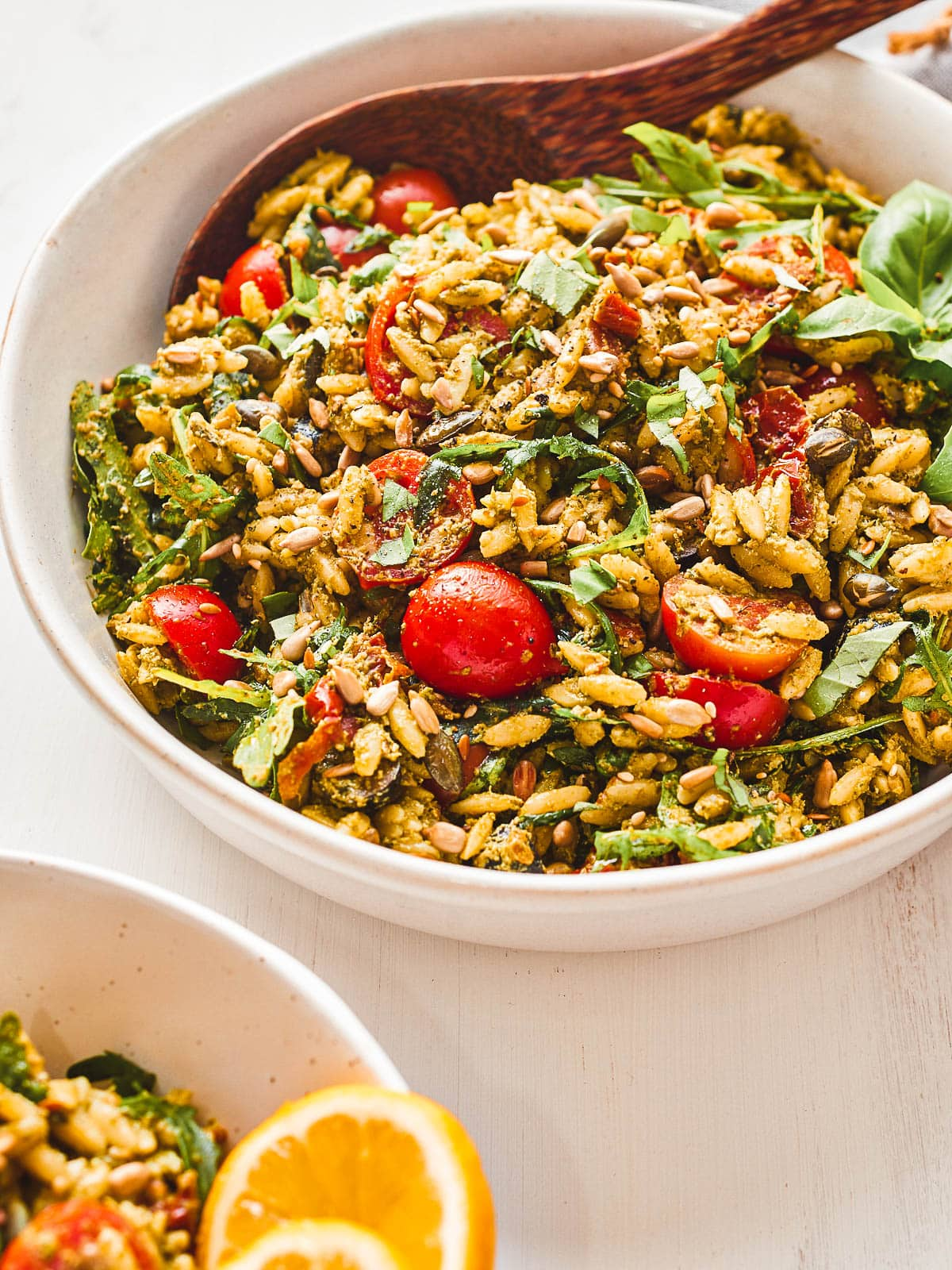 Serving bowl of pesto orzo salad with a served up portion on the side
