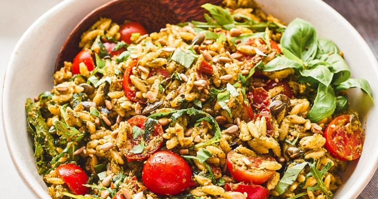 Serving bowl with pesto orzo salad and a small bowl with pasta salad and lemon slices behind
