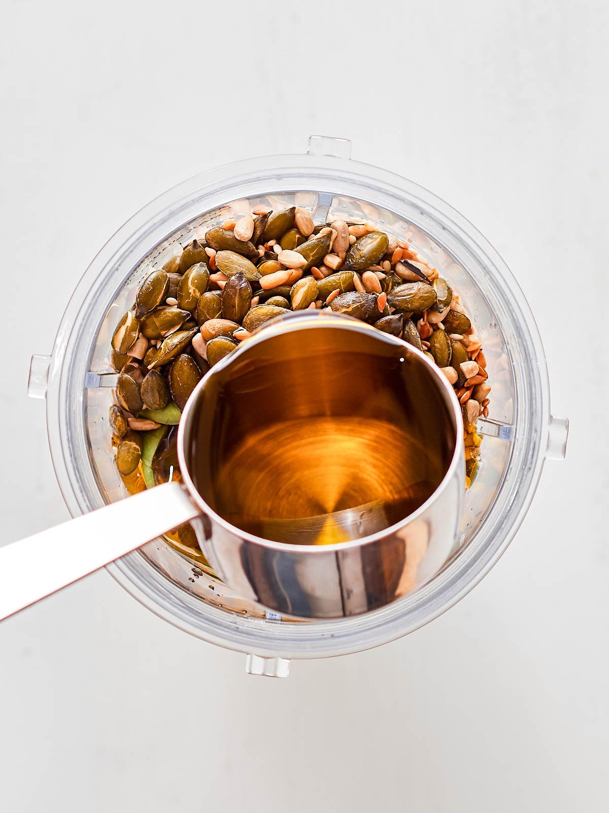 Adding olive oil to the blender