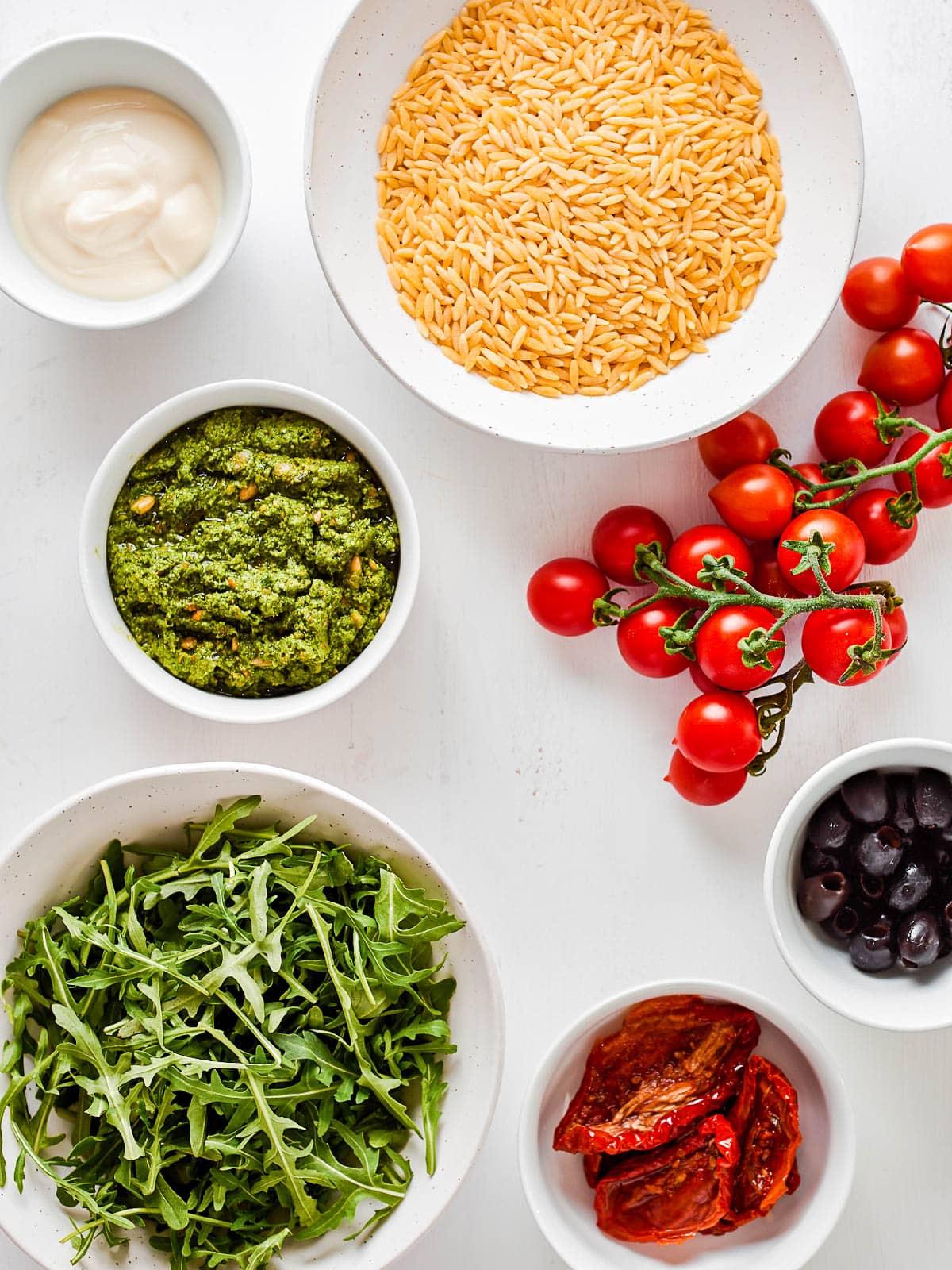 Ingredients for pesto orzo salad- orzo, tomatoes, olives, sun dried tomatoes, arugula, pesto, yoghurt
