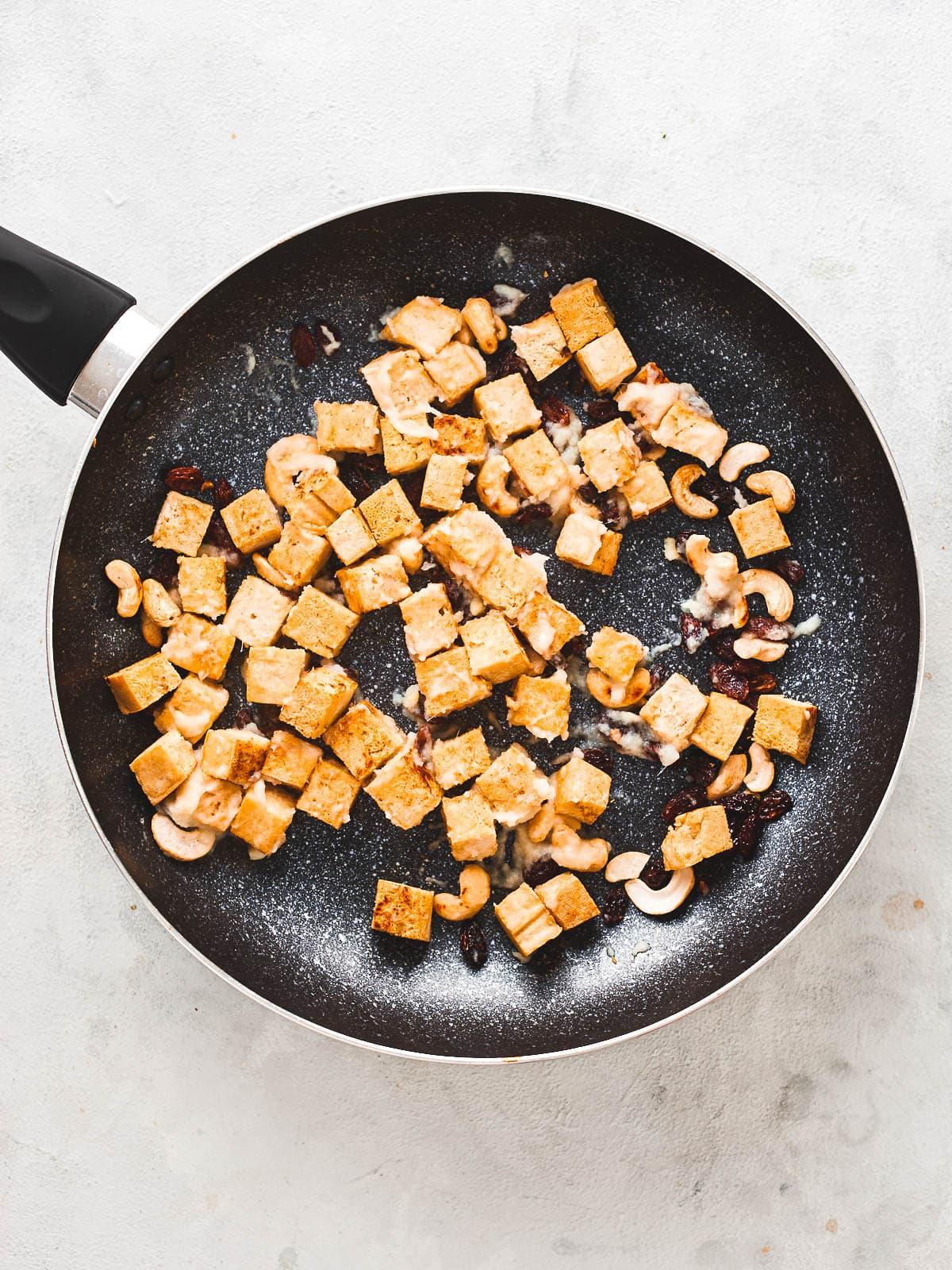 Paste stirred around in the pan with tofu, cashews and raisins